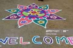 """Amazing kolam art of a flower andn """"Welcome"""" done with coloured chalk and flower pedals.Kolam and rangoli are types of Indian floor art made with chalk, rice powder and/or flowers.Photo taken in Kanchipuram (alt spelt Kancheepuram), Tamil Nadu, India."""